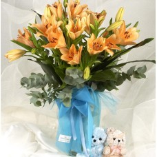 Lilies in a vase and a small teddy bear