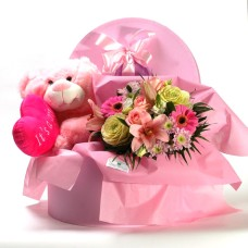 Teddy bear and flowers in a box